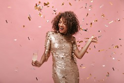 Young lady with short brunette hair in shiny stylish dress posing with glass with wine and with confetti on isolated backdrop..