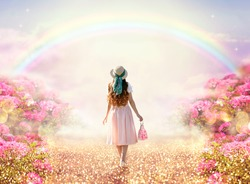 Young lady woman in romantic pink dress, retro hat, bag walking along rose garden path leading to fabulous rainbow unicorn house, flecks of sunlight on road. Tranquil fantasy scene, fairytale hills.