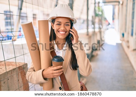 Young latin architect girl holding blueprints and using smartphone at the city.