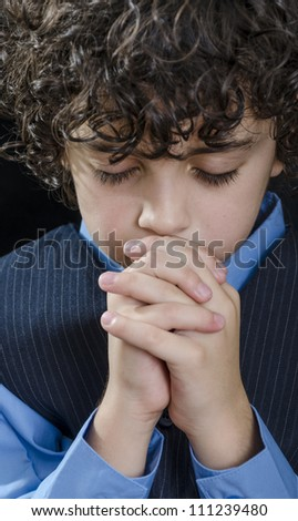 Young Latin boy praying and praising God