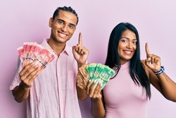 Young latin couple holding south african rand banknotes smiling with an idea or question pointing finger with happy face, number one