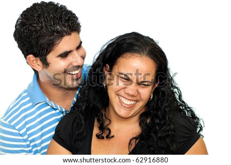 Young latin couple hugging and laughing isolated on a white background