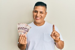 Young latin man holding 500 mexican pesos banknotes smiling with an idea or question pointing finger with happy face, number one