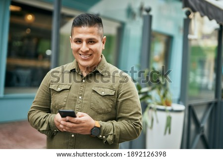 Young latin man smiling happy using smartphone at the city. Stok fotoğraf ©