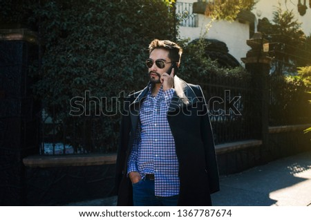 Young latin man talking casually on a cellphone