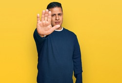 Young latin man wearing casual clothes doing stop sing with palm of the hand. warning expression with negative and serious gesture on the face.