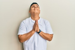 Young latin man wearing casual white t shirt begging and praying with hands together with hope expression on face very emotional and worried. begging.