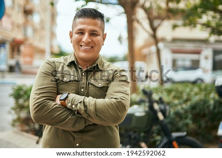 Young latin man with arms crossed smiling happy at the city. Stok fotoğraf ©