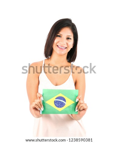 Young latin woman holding the flag of Brasil against a white background #1238590381