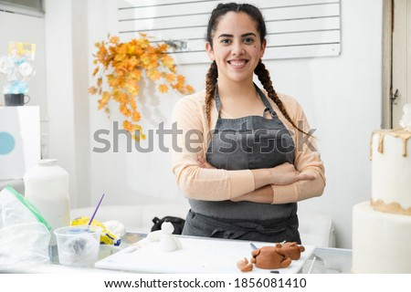 Young latin woman proud in her pastry shop - woman with crossed arms looking at the camera in her cake workshop - enterprising Hispanic woman