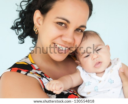 Young latin woman smiling and carrying her small baby girl