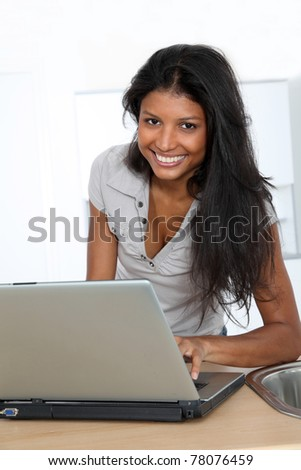 Young latin woman using laptop computer in home kitchen