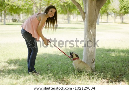 Young latin woman walking her dog at a park