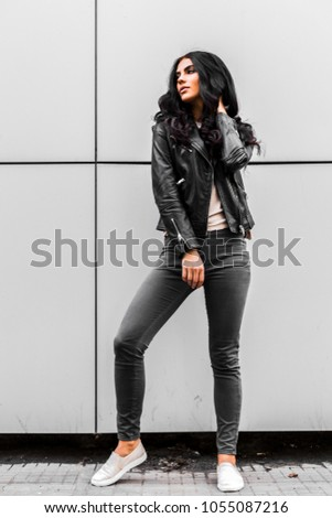 young latin woman walking with happy emotion on grey wall #1055087216