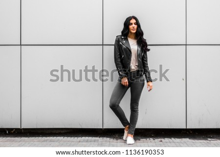 young latin woman walking with happy emotion on grey wall #1136190353