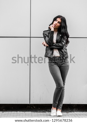 young latin woman walking with happy emotion on grey wall #1295678236