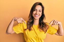 Young latin woman wearing casual clothes looking confident with smile on face, pointing oneself with fingers proud and happy.