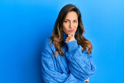 Young latin woman wearing casual winter sweater thinking concentrated about doubt with finger on chin and looking up wondering