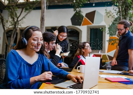 Young latin woman working with computer and her coworkers at the office or coworking in Mexico or South America, Mexican teamwork Foto stock ©