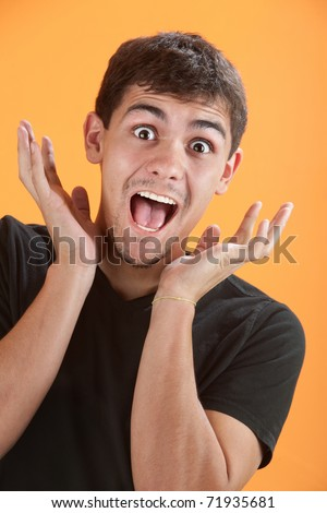 Young Latino man is very excited with hands near head