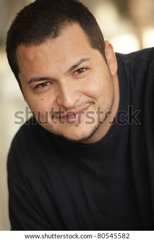 Young Latino man smiling - stock photo