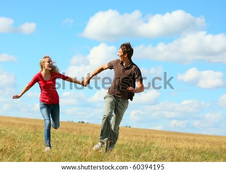 Young laughing couple running on meadow holding each other hands - stock photo
