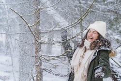 Young laughing funny happy girl, woman ,covered by snow walks in beautiful winter forest among trees, firs. Magnificent nature and views. Fashionable image, clothes, parka, hat, mittens, blue jeans.