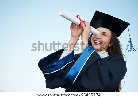 Young laughing graduate girl student in gown looking through diploma outdoors