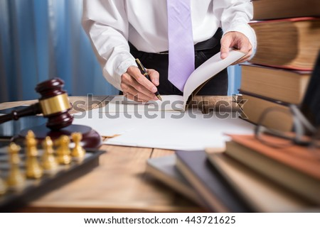Young lawyer business man working with paperwork on his desk in office workplace, consultant lawyer concept, hipster view of photography.