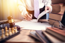 Young lawyer business man working with paperwork on his desk in office workplace for consultant lawyer concept of photography vintage tone with sunlight effect.