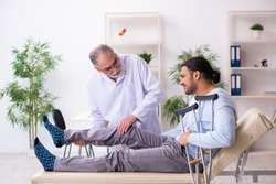 Young leg injured man visiting old doctor osteopath