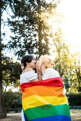 Young lesbian couple in love kissing in a park with a gay flag with trees in the background on a sunny summer day celebrating pride day.