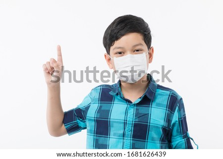 Young little Asain boy wearing surgical protective mask on face on white background and look at camera and point finger to black space. Idea for health care and prevent kid from risk of corona virus