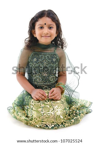 Young little Asian Indian girl smiling and sitting on white background
