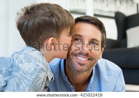 Young little boy giving a kiss on father cheek. Cute child kissing her dad at home. Loving son playing with his father.