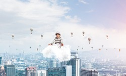 Young little boy keeping eyes closed and looking concentrated while meditating on cloud in the air with cityscape view and flying aerostats on background.