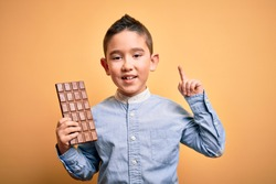 Young little boy kid eating sweet chocolate bar for dessert over isolated yellow background surprised with an idea or question pointing finger with happy face, number one