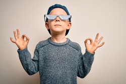 Young little caucasian kid wearing internet meme thug life glasses over isolated background relax and smiling with eyes closed doing meditation gesture with fingers. Yoga concept.