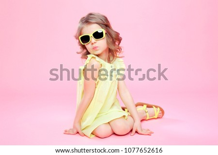Young little girl in yellow dress and sunglasses sitting on pink background in studio and giving a kiss.