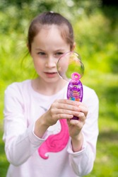 Young, little girl makes soap bubbles outdoor, summer fun activity for kids.