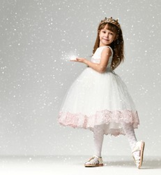 Young little girl model in the white communion  winter dress stands in gold crown with expensive gems under heavy snow in studio on grey background
