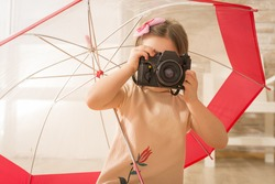 Young little girl photographer with old vintage photo camera taking picture sitting under umbrella, indoor shot. Beautiful girl using vintage photo camera. Children's play. Art or creativity concept.