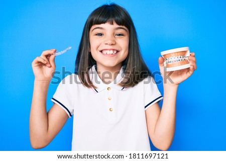 Young little girl with bang holding invisible aligner orthodontic and braces smiling with a happy and cool smile on face. showing teeth.
