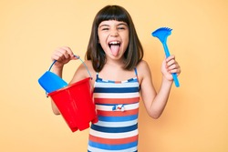 Young little girl with bang playing with summer shovel and bucket toys sticking tongue out happy with funny expression.