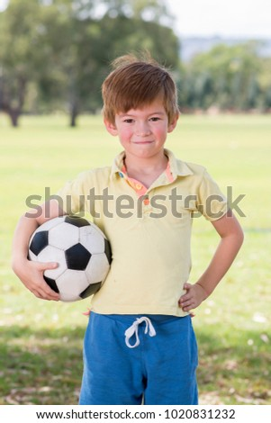 young little kid 7 or 8 years old enjoying happy playing football soccer at grass city park field posing smiling proud standing holding the ball in childhood sport passion and healthy lifestyle