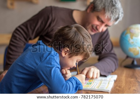 Young little shoolboy solving mathematics homework with father, cooperation in family, parenthood