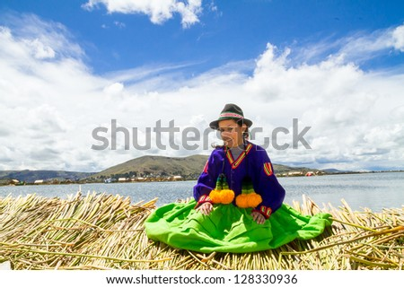 Young local girl on a floating Uros island standing in front of her home, lake Titicaca