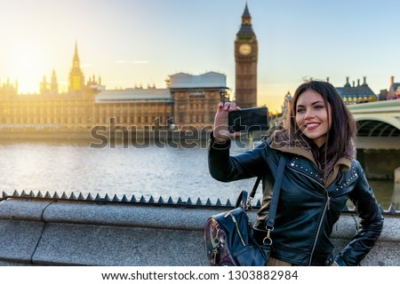 Young London traveller woman takes selfie pictures with her phone at Westminster with view to the Big Ben Tower in London, UK, during sunset time