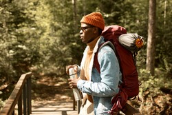 Young lonely explorer enjoy view from bridge. Guy with thermos flask and big backpack for camping. Trip to forest, hiking in mountains. Travelling, escape loud city, freedom concept