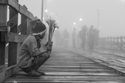 Young lonely poor boy selling flowers at Mon wooden bridge in cold morning mist, Sangkhlaburi Kanchanaburi Thailand